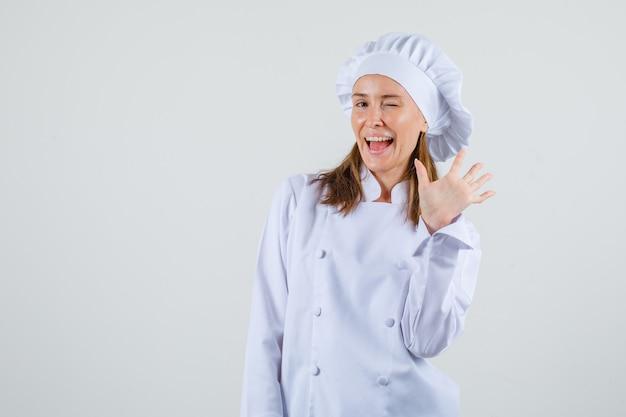 Vrouwelijke chef-kok zwaaiende hand met knipperende ogen in wit uniform en energiek op zoek