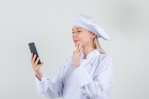 Vrouwelijke chef-kok zwaaiende hand op videocall in wit uniform en op zoek vrolijk