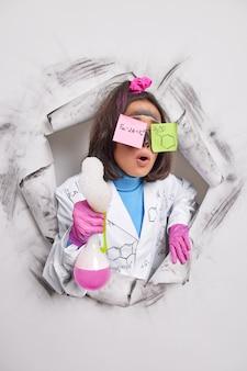 Vrouwelijke chemicus heeft stickers op ogen geplakt met geschreven formules houdt fles met roze vloeistofbellen draagt witte jas rubberen handschoenen houdt mond open van verwondering breekt door papiergat