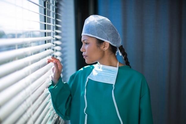Vrouwelijke chirurg die door venster kijkt