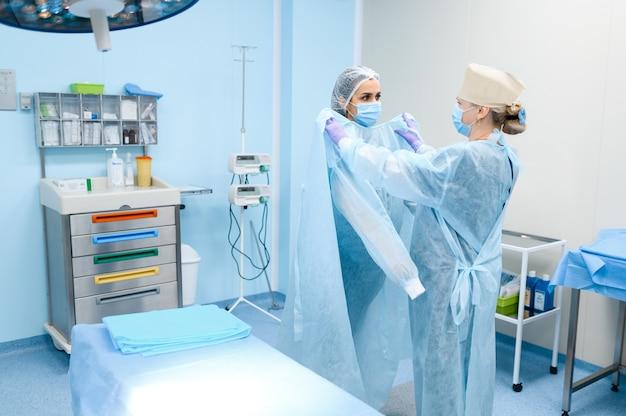 Vrouwelijke chirurg en assistent in operatiekamer, operatie voorbereiden