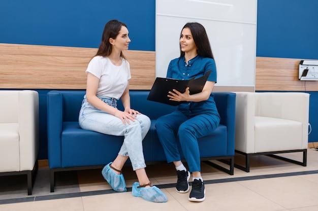 Vrouwelijke chirurg en patiënt zittend op de bank in de hal van de kliniek