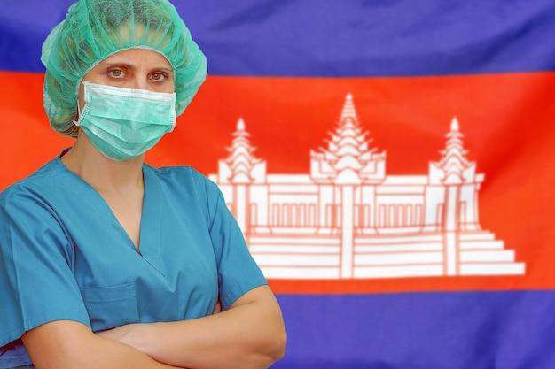 Vrouwelijke chirurg in masker en hoed kijkt naar de camera op de achtergrond van de vlag van cambodja