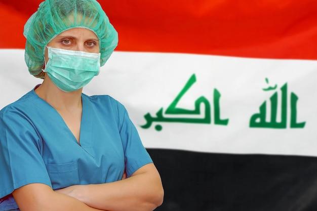 Vrouwelijke chirurg in masker en hoed kijkt naar de camera op de achtergrond van de vlag van irak