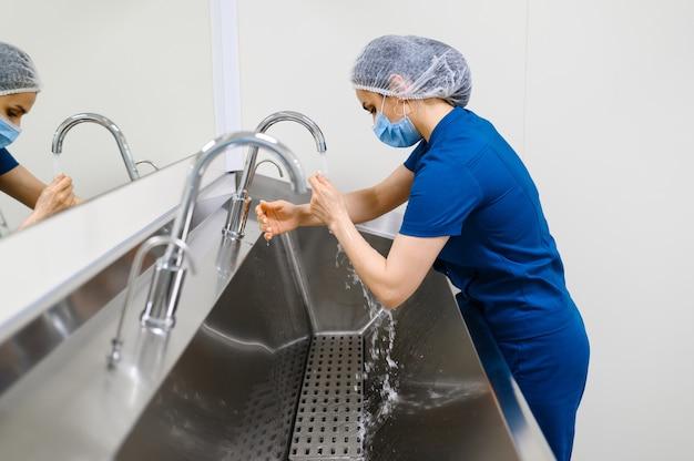 Vrouwelijke chirurg in masker wast handen, chirurgie operatie voorbereiden