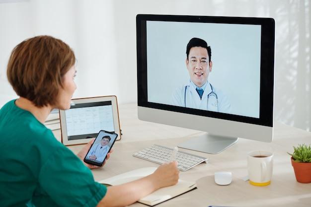 Vrouwelijke chirurg video bellen met haar collega's om advies te vragen en schrijven in notitieblok