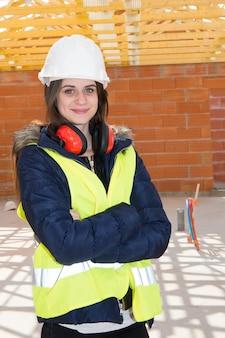 Vrouwelijke civiel-ingenieurs die beschermende vesten en bouwvakkers dragen die op bouwwerf controleren