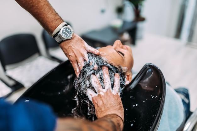 Vrouwelijke cliënt die hoofdmassage en haar krijgt dat in de salon wordt gewassen.