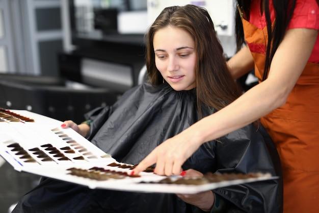 Vrouwelijke cliënt met meester in schoonheidssalon onderzoekt monsters van palet van haarkleurmiddelen