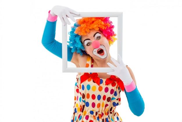 Vrouwelijke clown die in kleurrijke pruik een wit frame houdt.
