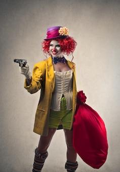 Vrouwelijke clown met een pistool