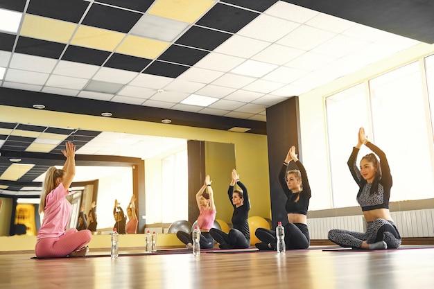 Vrouwelijke coach in yogales leert meditatie in de klas met blanke groep mensen