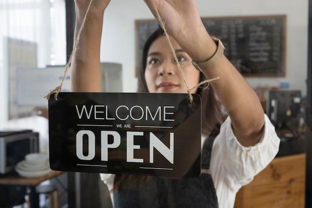 Vrouwelijke coffeeshopeigenaar die het open teken op een glazen deur hangt.