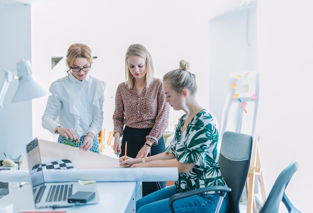 Vrouwelijke collega die bedrijfsproject bespreken op het werk in het bureau