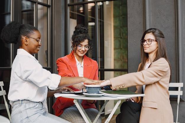 Vrouwelijke collega's bespreken gegevens in het café buiten. multiraciale vrouwelijke personen die productieve strategie analyseren voor zakelijke projectie met behulp van documenten in straatcafé