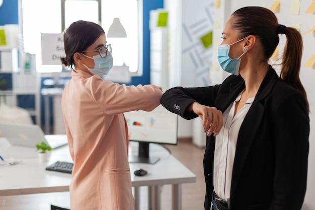 Vrouwelijke collega's die de elleboog aanraken met een gezichtsmasker in een nieuw normaal kantoor tijdens de wereldwijde pandemie met covid19-griep die sociale afstand houdt als preventie om infectie te voorkomen.