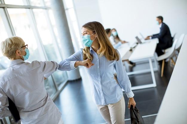 Vrouwelijke collega's die sociale afstand houden, elkaar begroeten door tegen ellebogen te stoten, om te voorkomen dat covid 19 coronavirus-infectie zich verspreidt