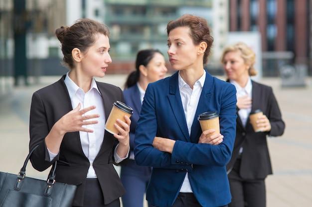 Vrouwelijke collega's met afhaalmaaltijden koffiemokken samen wandelen in de stad, praten, project bespreken of chatten. gemiddeld schot. werk pauze concept