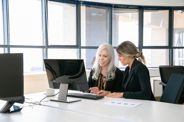 Vrouwelijke collega's zitten samen op de werkplek, met behulp van computer in de buurt van papieren diagram. zakelijke communicatie of mentorschap concept