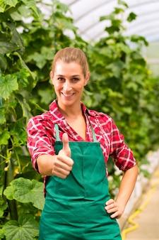 Vrouwelijke commerciële tuinman in groen huis