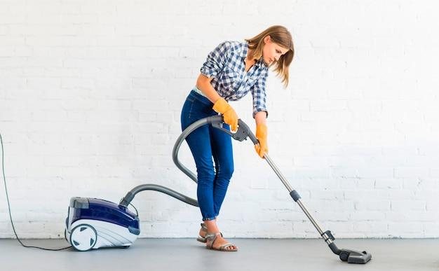 Vrouwelijke conciërge schoonmakende vloer met stofzuiger
