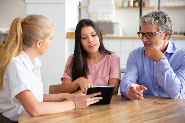 Vrouwelijke consultant of manager ontmoeting met een aantal jonge en volwassen klanten, inhoud presenteren op tablet