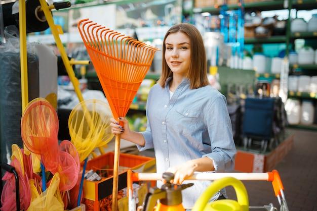 Vrouwelijke consument die tuingereedschap in de winkel voor tuinlieden kiest. vrouw die apparatuur in de winkel koopt voor de bloementeelt, de aankoop van het bloemistinstrument