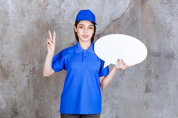 Vrouwelijke de dienstagent die in blauw uniform een ovale infobord houdt en positief handteken toont.