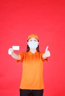 Vrouwelijke de dienstagent in eenvormige oranje kleur en masker dat haar visitekaartje voorstelt en positief handteken toont.