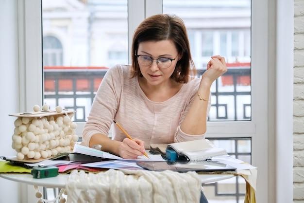Vrouwelijke decorateur die met materiaalmonsters werkt, stoffen selecteert en modellen van gordijnen tekent