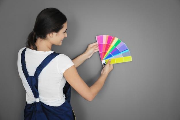 Vrouwelijke decorateur met kleurenpaletmonsters tegen grijs