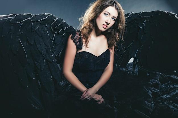 Vrouwelijke demon met zwarte vleugels kostuum in carnaval en religieuze stijl op een zwarte achtergrond