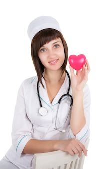 Vrouwelijke die arts met hart op een witte achtergrond wordt geïsoleerd