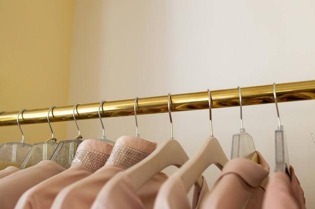 Vrouwelijke dingen van roze kleur op een hangerclose-up. nieuwe collectie in de winkel.