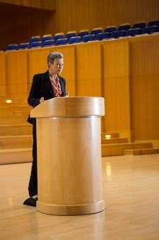 Vrouwelijke directeur die een toespraak houdt op conferentiecentrum