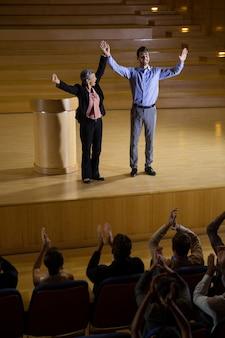 Vrouwelijke directeur waardeert een collega op het podium in het conferentiecentrum