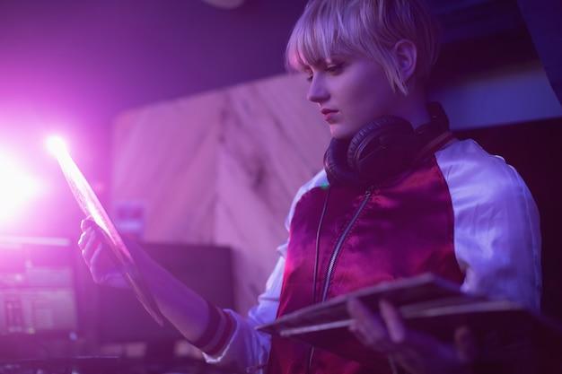 Vrouwelijke dj die een vinylplaatrecord in staaf houdt