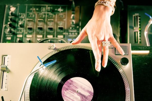 Vrouwelijke dj op de draaitafel in club