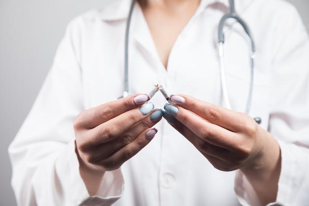 Vrouwelijke dokter breekt sigaret