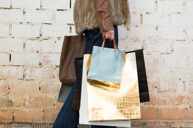 Vrouwelijke dragende het winkelen zakken dichtbij muur