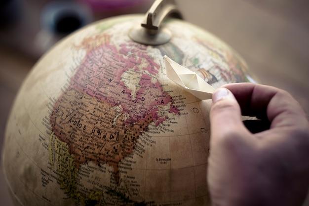 Vrouwelijke dromer reislust mensen spelen met de hand met een kleine papieren boot op een wereldbol die ervoor kiest en zich voorstelt om te reizen en naar een nieuwe bestemming te komen. vakantie- en levensstijlplanning