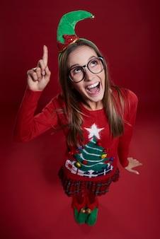Vrouwelijke elf met vinger omhoog gekleed in kerstkleren
