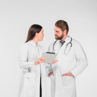 Vrouwelijke en mannelijke artsen bespreken en kijken naar elkaar