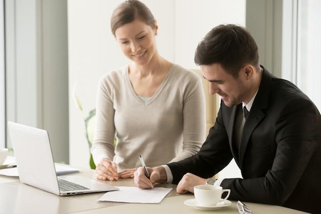 Vrouwelijke en mannelijke bedrijfsleiders die contract ondertekenen
