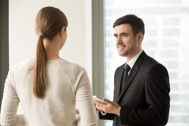 Vrouwelijke en mannelijke collega's die in bureau samenkomen