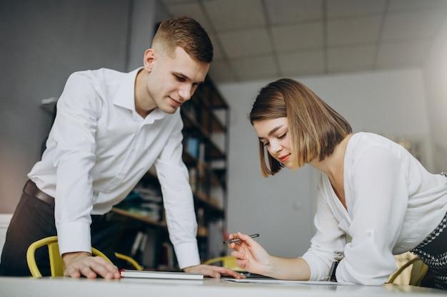 Vrouwelijke en mannelijke collega's die in bureau werken