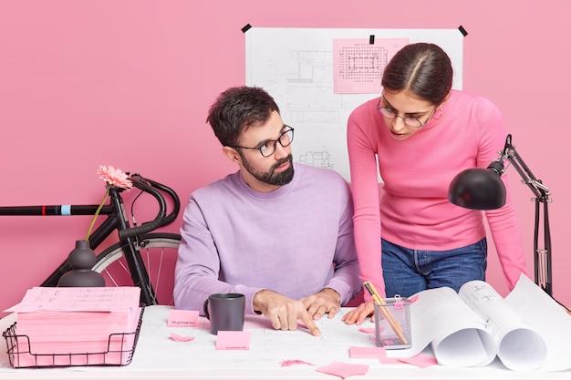Vrouwelijke en mannelijke collega's genieten van coworking-proces, bespreken iets, raadplegen elkaar druk bezig met het ontwerpen van projecten, poseren op het bureaublad, delen meningen terwijl ze schetsen controleren. samenwerkingsconcept: