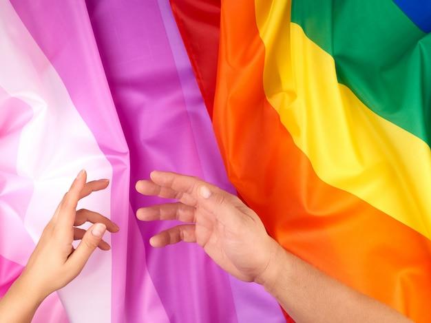 Vrouwelijke en mannelijke hand uitgestrekt tegen de achtergrond van vlaggen van lgbt-gemeenschappen