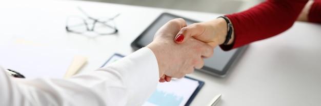 Vrouwelijke en mannelijke handdruk in kantoor close-up