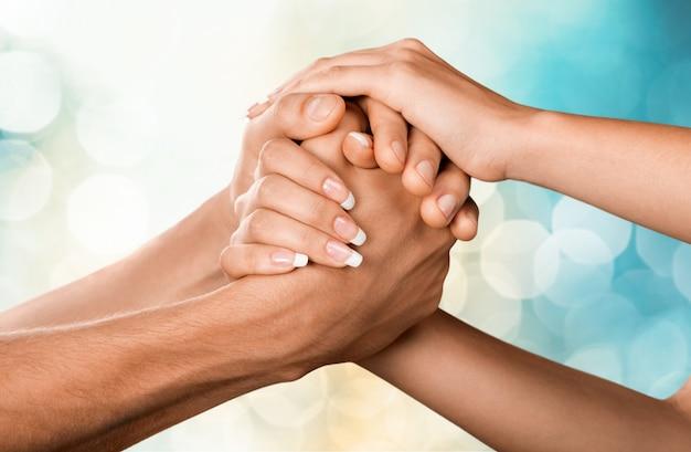 Vrouwelijke en mannelijke handen die elkaar op de achtergrond houden